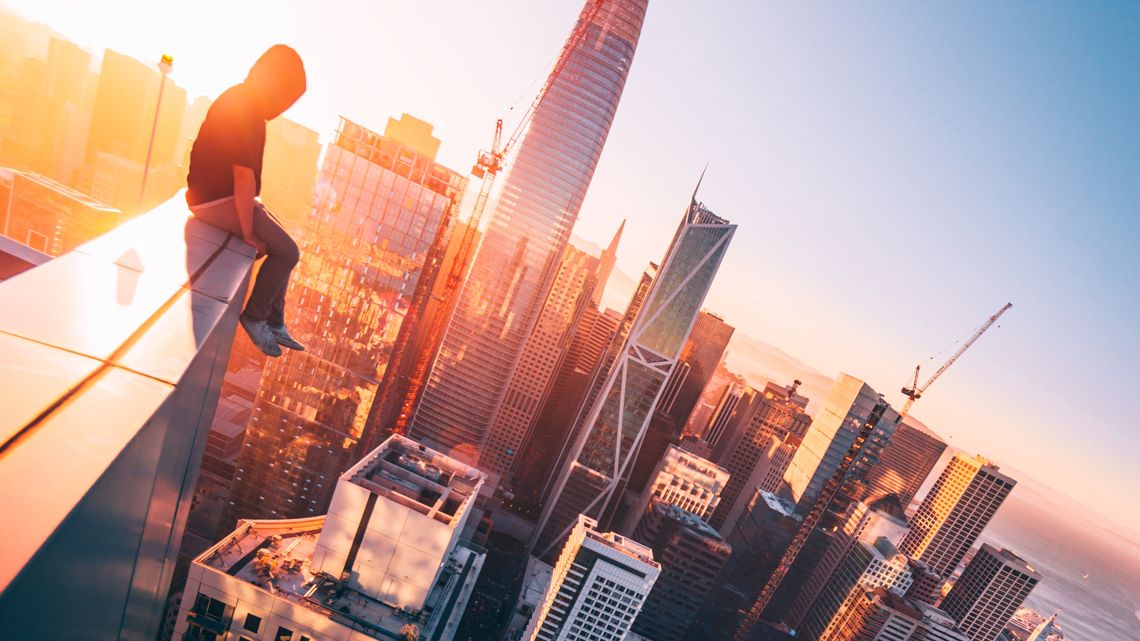 a person sitting on the top of a tall building hd photography 4k