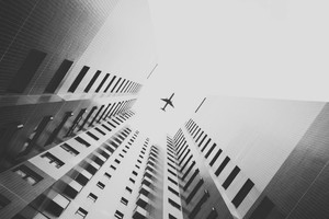 Airplane Flying Above Skyscrapers