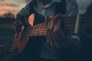 Boy Playing Guitar Outdoors 5k Wallpaper