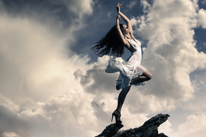 Brunette Girl Dancing On Mountain Top Clouds