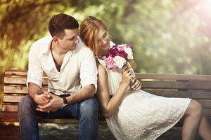 Couple Sitting On Bench With Flowers Wallpaper