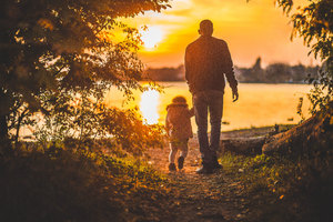 Father And Kid Walking Towards Lake