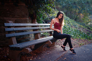 Girl Sitting On Bench Outdoors Wallpaper