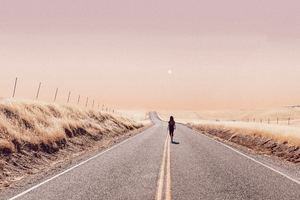 Girl Walking Alone On Desert Road Wallpaper