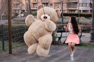 Girl With Big Teddy Bear On Swing