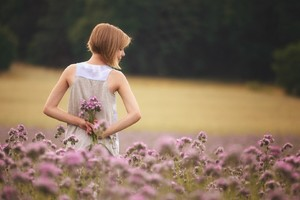 Girl With Flowers Standing In Field Wallpaper