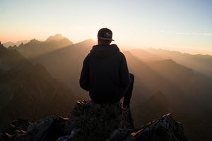 Man With Cap Sitting On The Mountain Edge Wallpaper