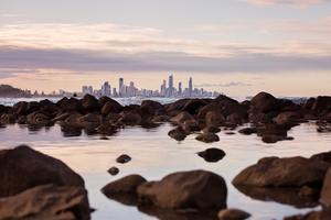 Seashore Rocks Near City View Of Buildings 5k Wallpaper