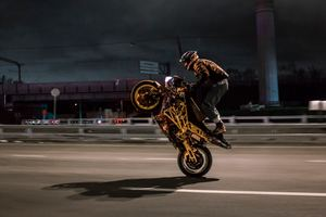 Urban Biker Doing Wheelie Wallpaper