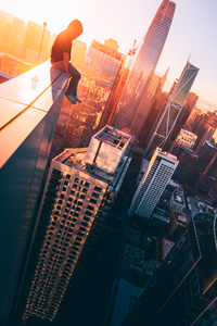 1080x2160 A Person Sitting On The Top Of A Tall Building