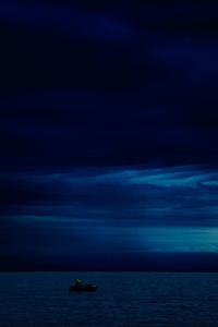 750x1334 Dark Evening Blue Cloudy Alone Boat In Ocean 5k