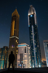 Man Standing Front Of Tall Buildings