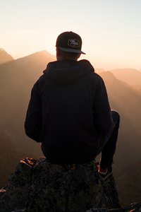 720x1280 Man With Cap Sitting On The Mountain Edge