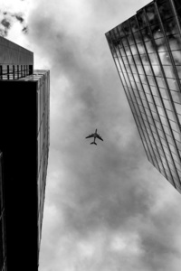 240x320 Plane Between Two Buildings Monochrome